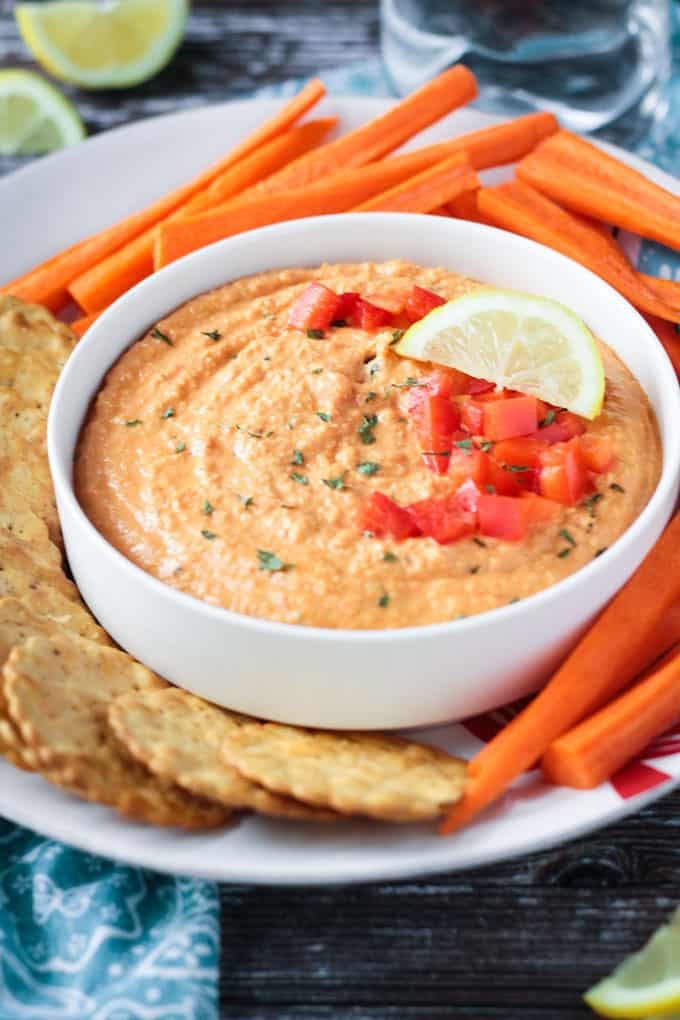 Bowl of roasted red pepper hummus topped with fresh chopped red bell peppers, chopped parsley, and a lemon wedge.