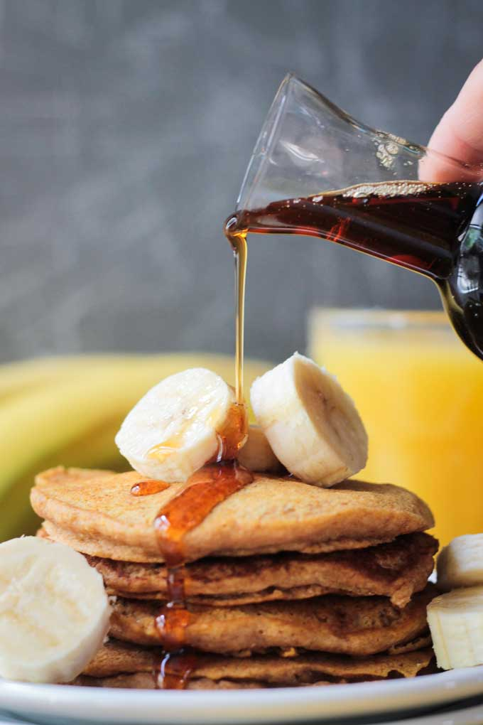 Small glass of maple syrup being poured over a stack of Banana Pumpkin Spice Pancakes.