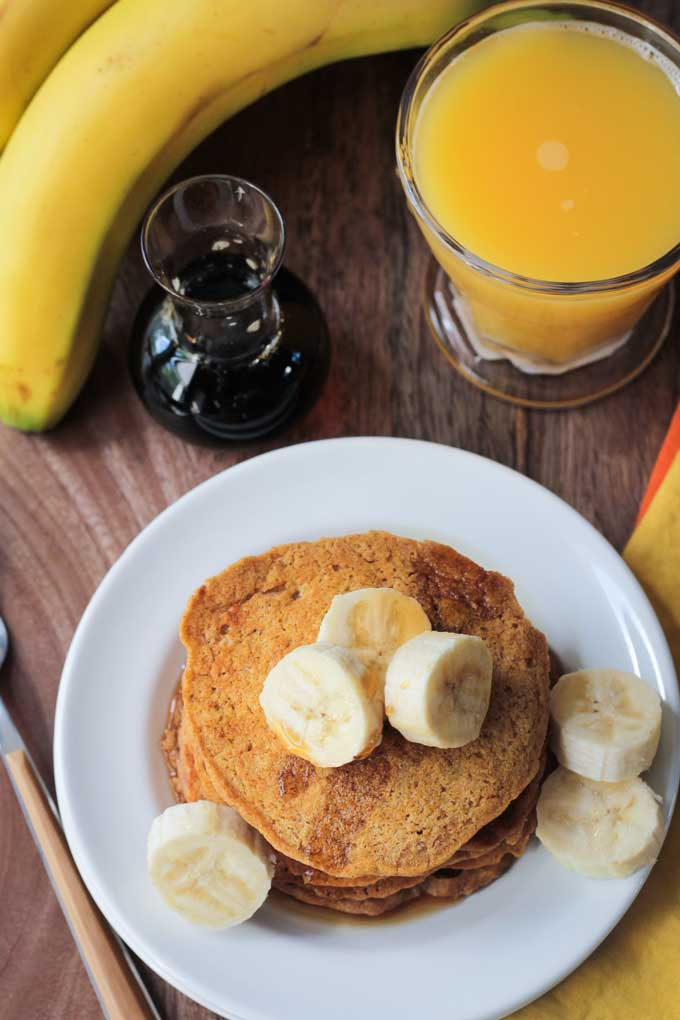 Overhead view of a plate of Banana Pumpkin Spice Pancakes topped with fresh sliced bananas. Glass or orange juice, small jar of maple syrup, and a bunch of bananas nearby.