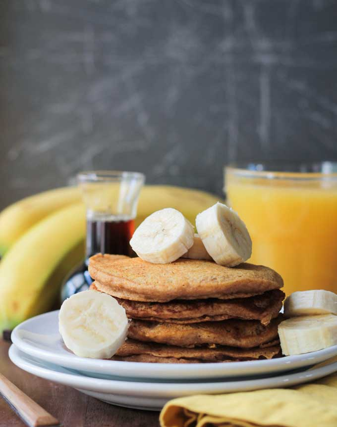 Stack of Banana Pumpkin Spice Pancakes topped with banana slices. Glass or orange juice and a bunch of bananas in the background.