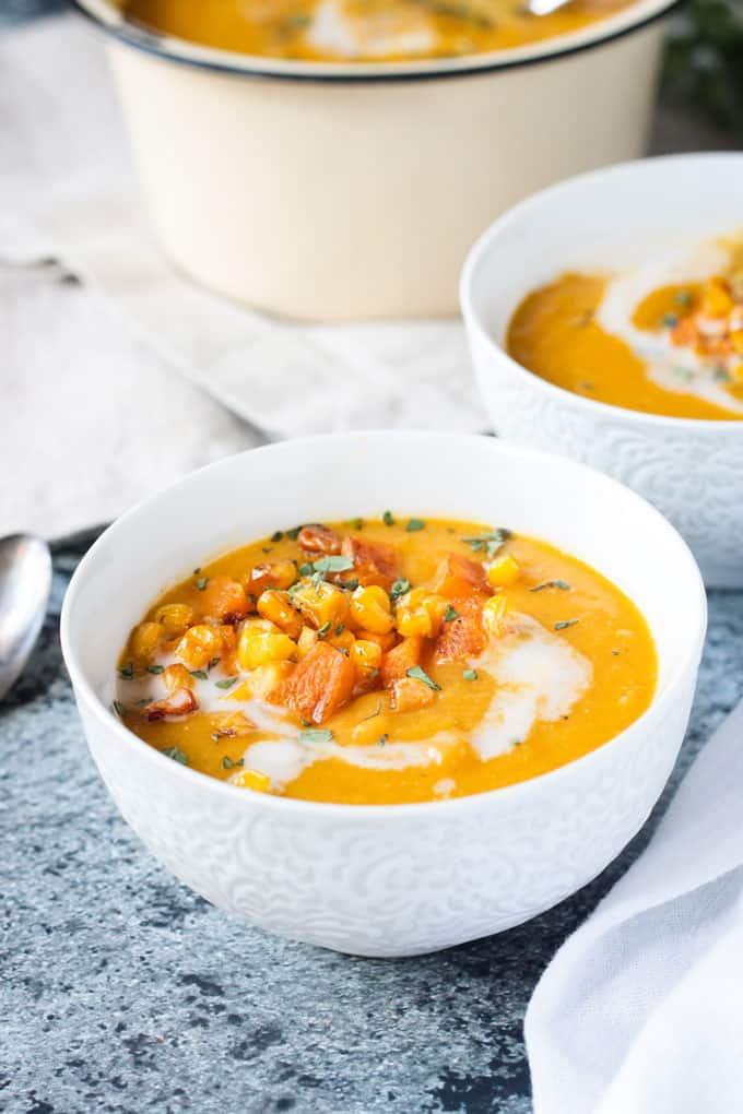 Close up front view of vegan butternut squash soup in a white bowl topped with diced squash, corn, and thyme.