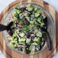 healthy broccoli salad in a glass serving bowl with salad forks