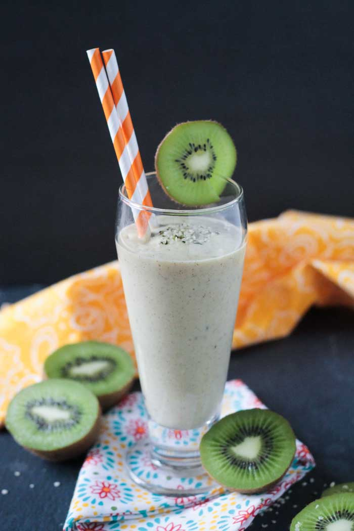 Mango Kiwi Smoothie with Hemp Hearts in a tall glass, kiwi slice on side of glass as a garnish, 2 orange and white striped straws in the glass. Fresh kiwi slices surrounding the glass on the table.