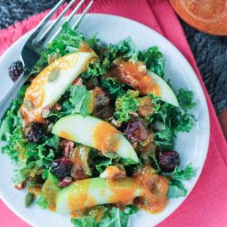 kale salad with apple slices and pumpkin dressing drizzled over the top