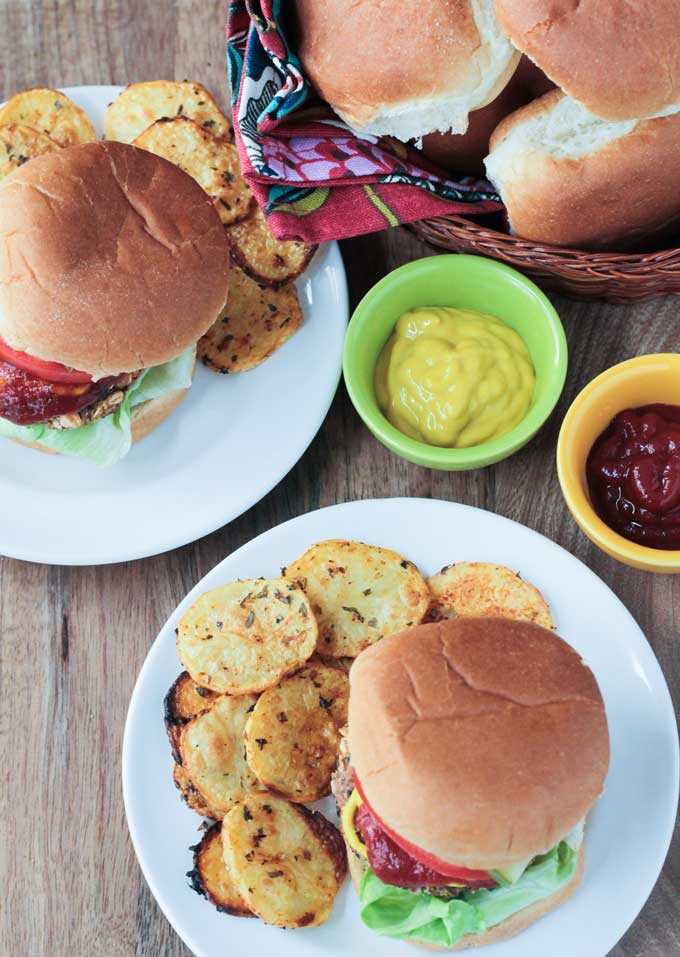 Two plates Black Bean Salsa Burgers paired with crispy potato rounds. Small bowls of ketchup and mustard and a basket of burger buns next to the plates.