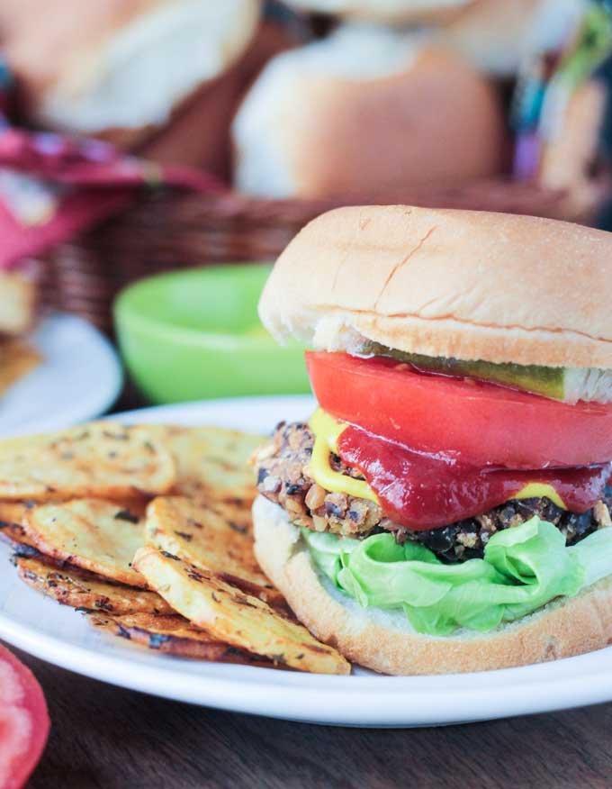 Black Bean Salsa Burgers with lettuce, tomato, pickles, ketchup, and mustard. Crispy potato rounds next to the burger on the plate.
