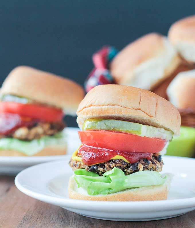 Front view of a black bean salsa burger on a bun with lettuce, tomato, pickle, ketchup, and mustard. Another plate with a burger in the background next to a basket of buns.