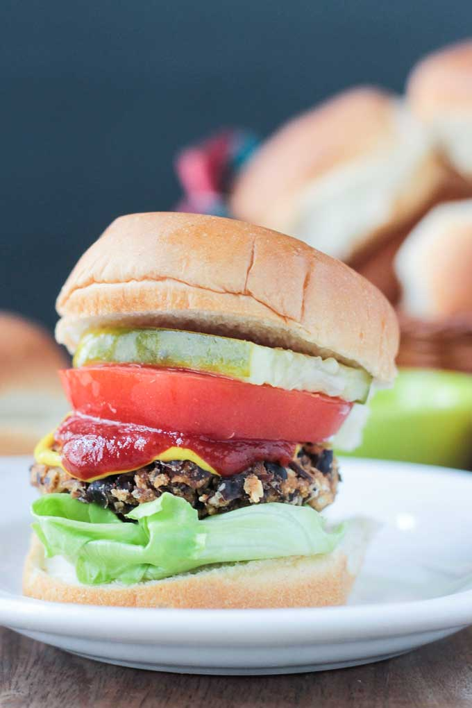 Close up of a Black Bean Salsa Burger on a bun with ketchup, mustard, lettuce, tomato, and pickle.