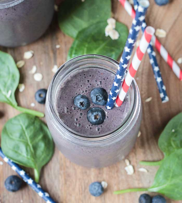 Blueberry Oatmeal Smoothie, on a wooden table, surrounded by fresh spinach leaves, fresh blueberries, and raw oats. Two red, white and blue straws in the glass.