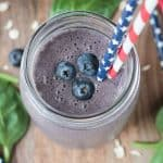 Overhead view of a blueberry oatmeal smoothie in a glass jar topped with three fresh blueberries.