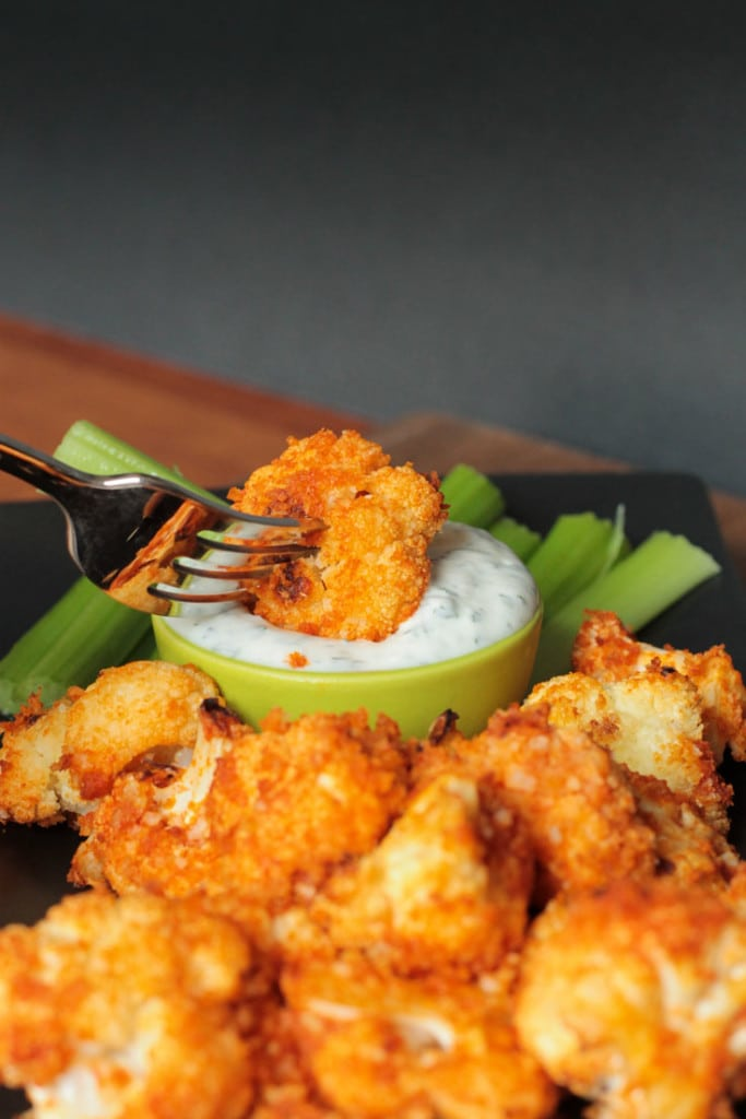 A buffalo cauliflower floret on a fork being dipped into ranch dressing. A pile of breaded florets on a tray in front. Celery sticks behind.