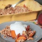 peach crisp on a gray plate topped with whipped cream