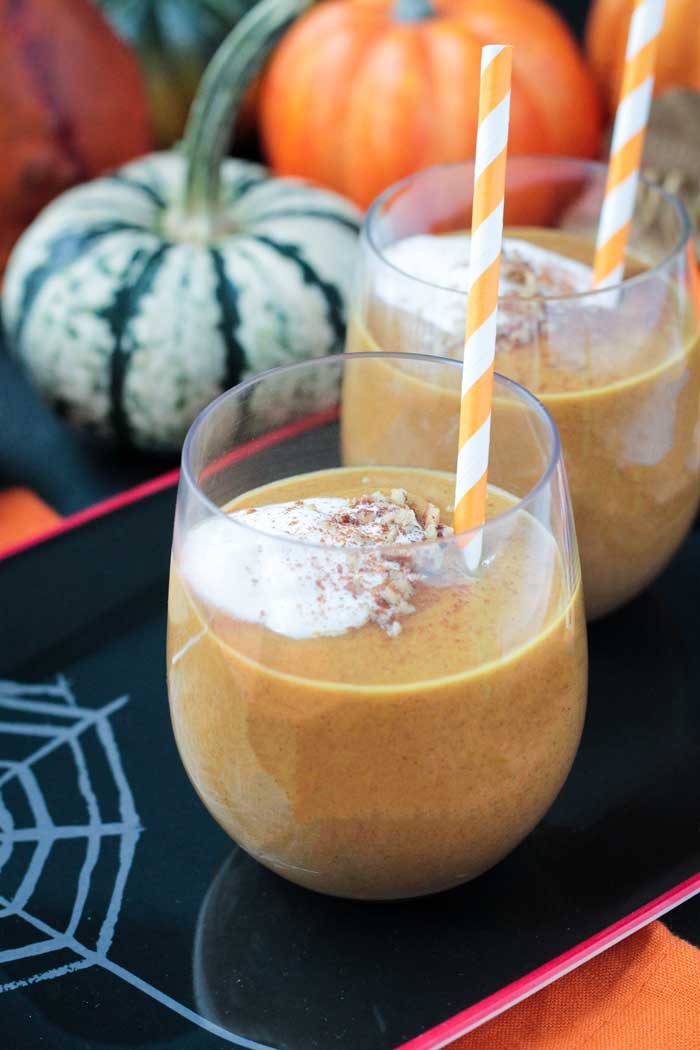 2 glasses of Pumpkin Pie Smoothie with orange and white striped straws on a black tray. Decorative pumpkins in the background.