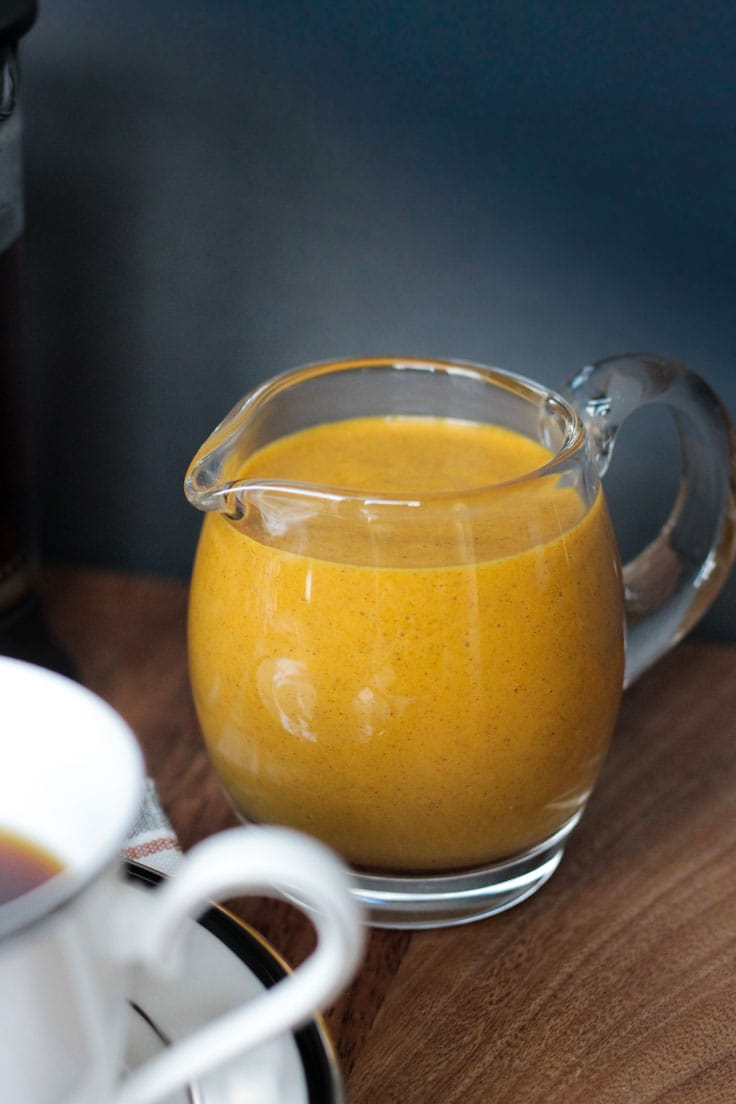 Orange hued creamer in a small glass pitcher.