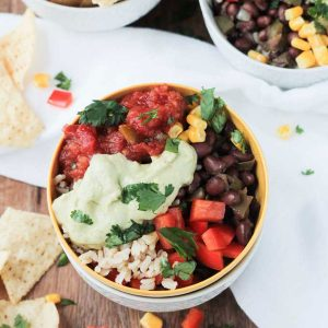 Rice, black beans, peppers, corn, salsa, and avocado sauce in a bowl