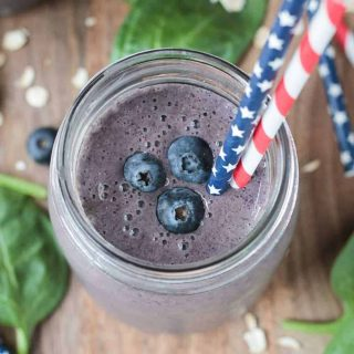 three fresh blueberries and two straws in a glass of blueberry smoothie