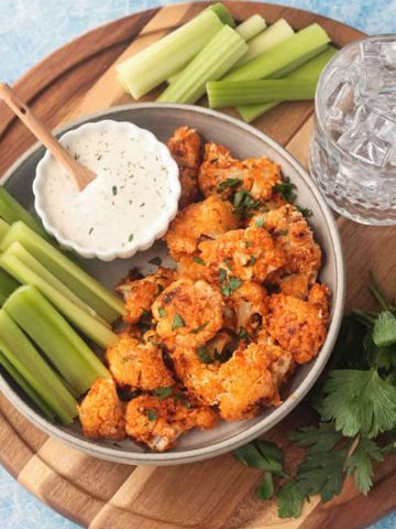 Plate of vegan buffalo cauliflower bites on a plate with celery sticks and small bowl of ranch.
