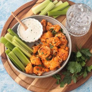 Overhead view of a plate of buffalo cauliflower bites with celery sticks and ranch dip on a round wooden tray with glass of water and bunch of parsley
