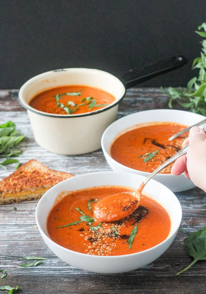 Spoonful of creamy vegan tomato soup being lifted out of a bowl of soup. Another bowl and a pot of soup behind.