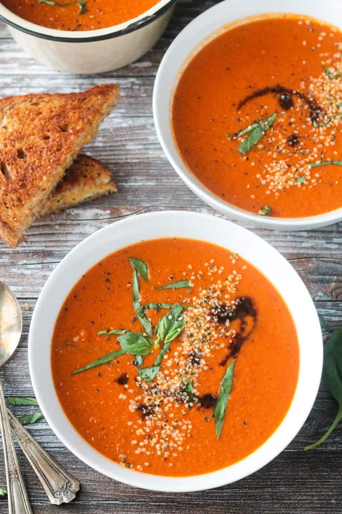 Two white bowls of tomato soup with garnishes.