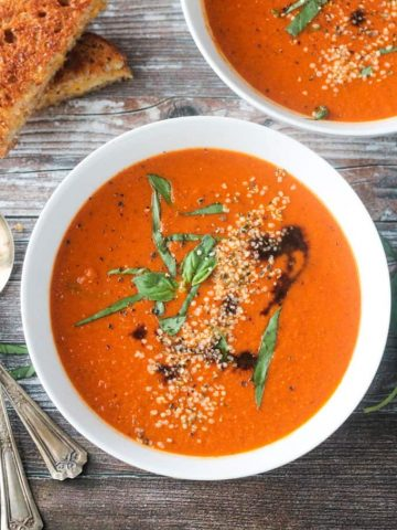 Close up overhead view of a bowl of vegan tomato soup topped with fresh basil, balsamic drizzle, and hemp seeds.