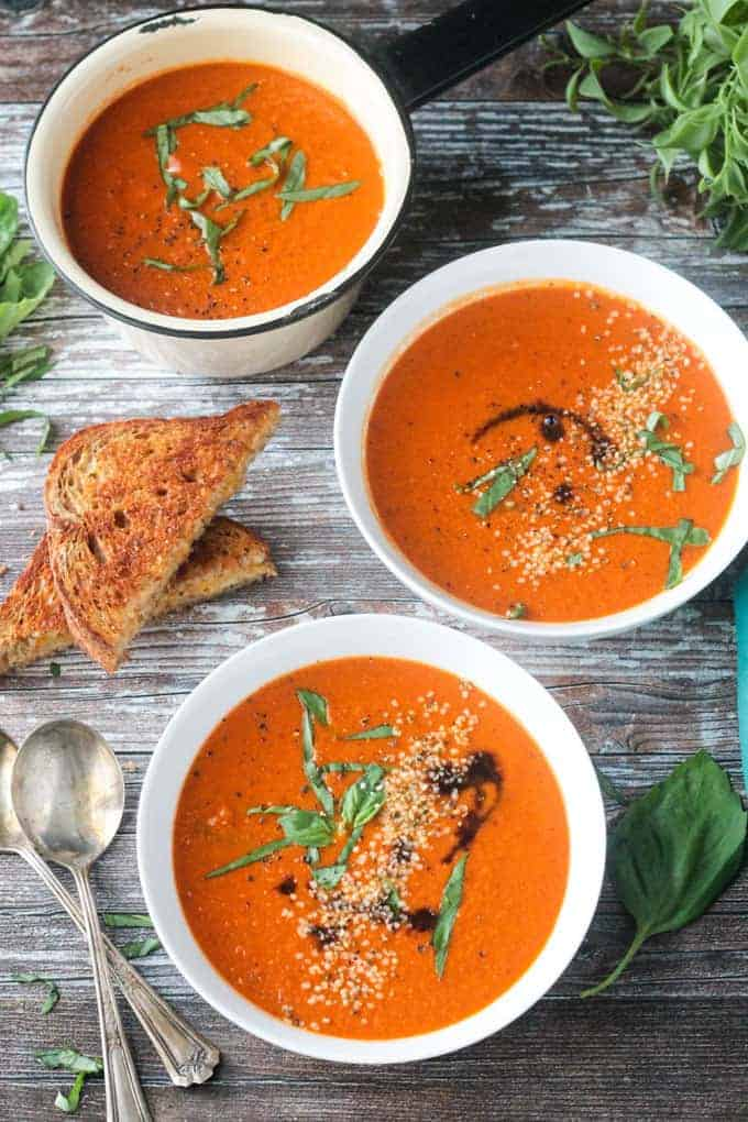 Three bowls of tomato soup on a brown wooden background with a grilled cheese sandwich and two spoons.