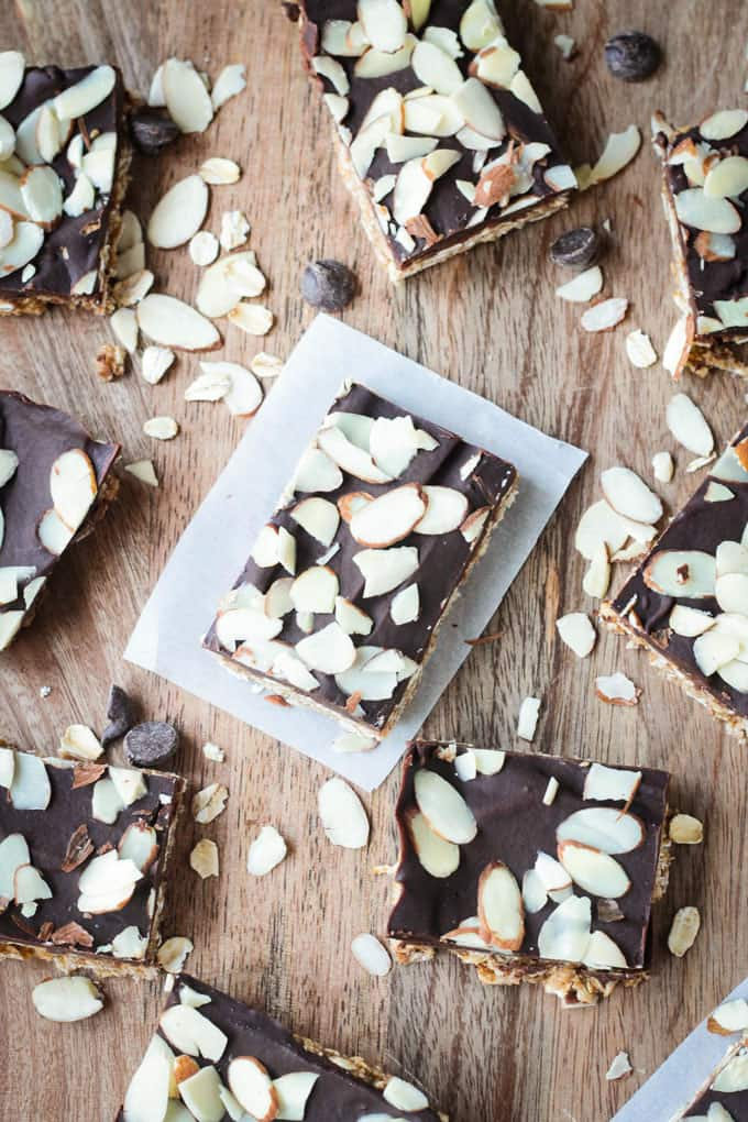 One triple almond oat bar on a square of parchment paper on a wooden tray. Garnished with slivered almonds.
