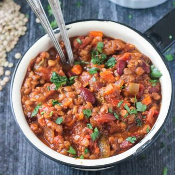 Pot of vegan pumpkin chili with two spoons.