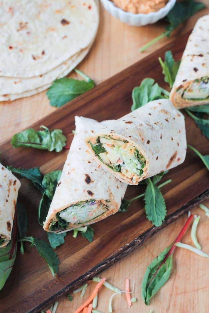 Overhead shot of veggie tortilla wraps on a wood serving board with leafy greens scattered nearby.