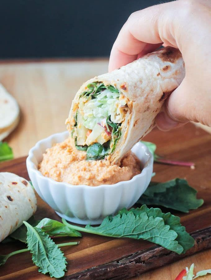 Tortilla veggie wrap dipping into a small white bowl of spicy hummus.