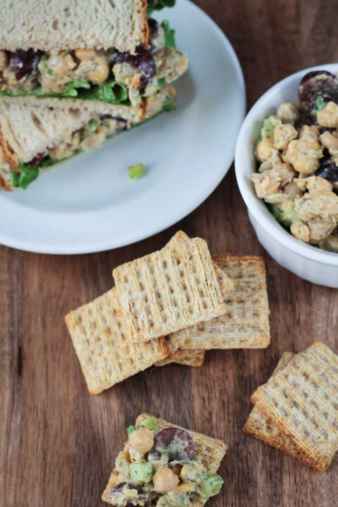 Vegan Chickpea Salad Sandwich on a white plate next to a bowl of chickpea salad. Whole wheat crackers in a pile on the table in front.