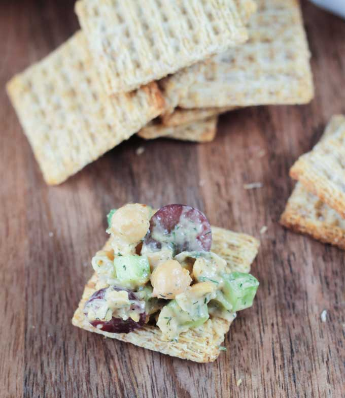 Vegan Chickpea Salad recipe on a whole wheat cracker. Pile of crackers behind.