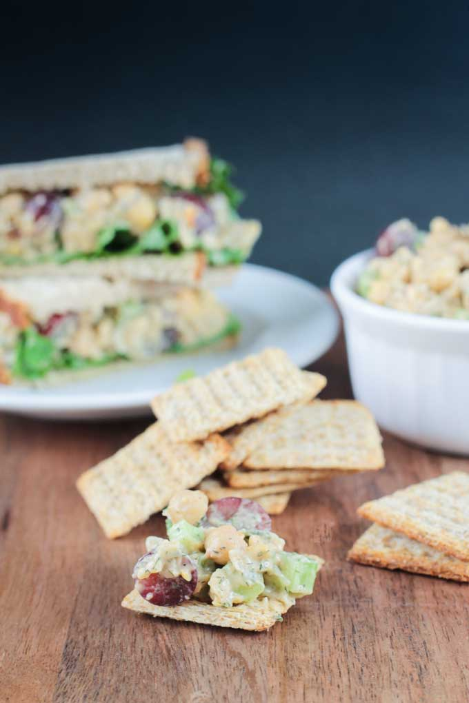 Vegan Chickpea Salad on a cracker in front of a pile of crackers and a chickpea salad salad sandwich on a plate.
