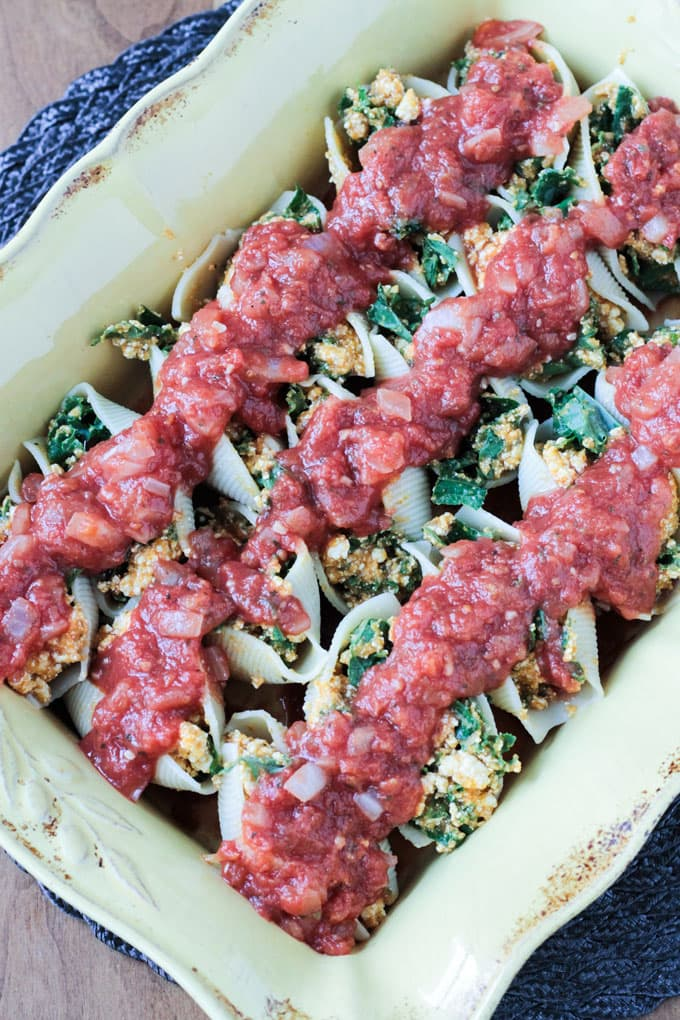 Yellow casserole dish full of Pumpkin & Kale Vegan Stuffed Shells and topped with marinara sauce.