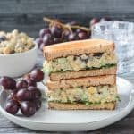 Stacked vegan chickpea salad sandwich halves on a plate with a bunch of red grapes.