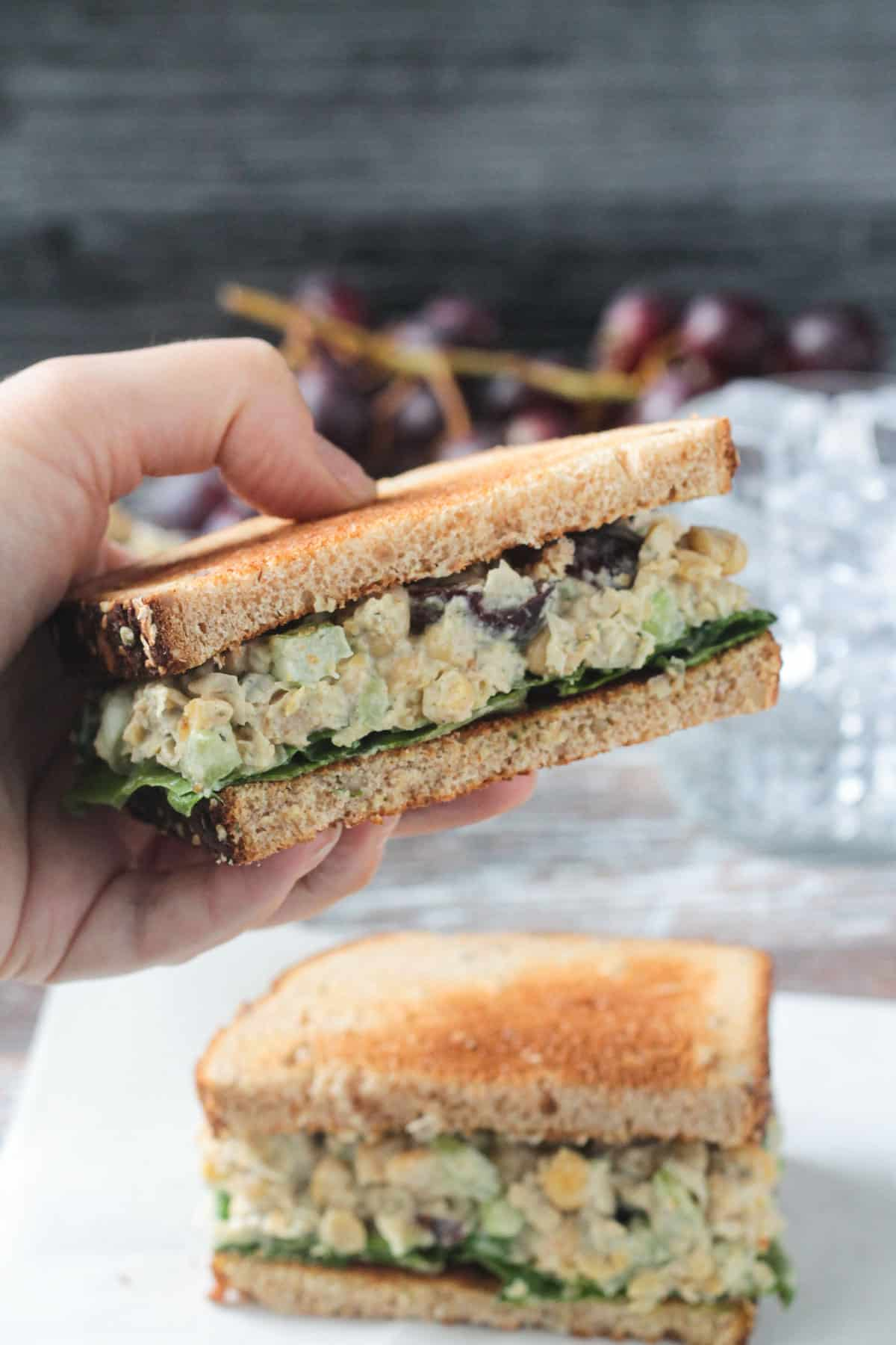 Hand holding up a half of a vegan chickpea salad sandwich.