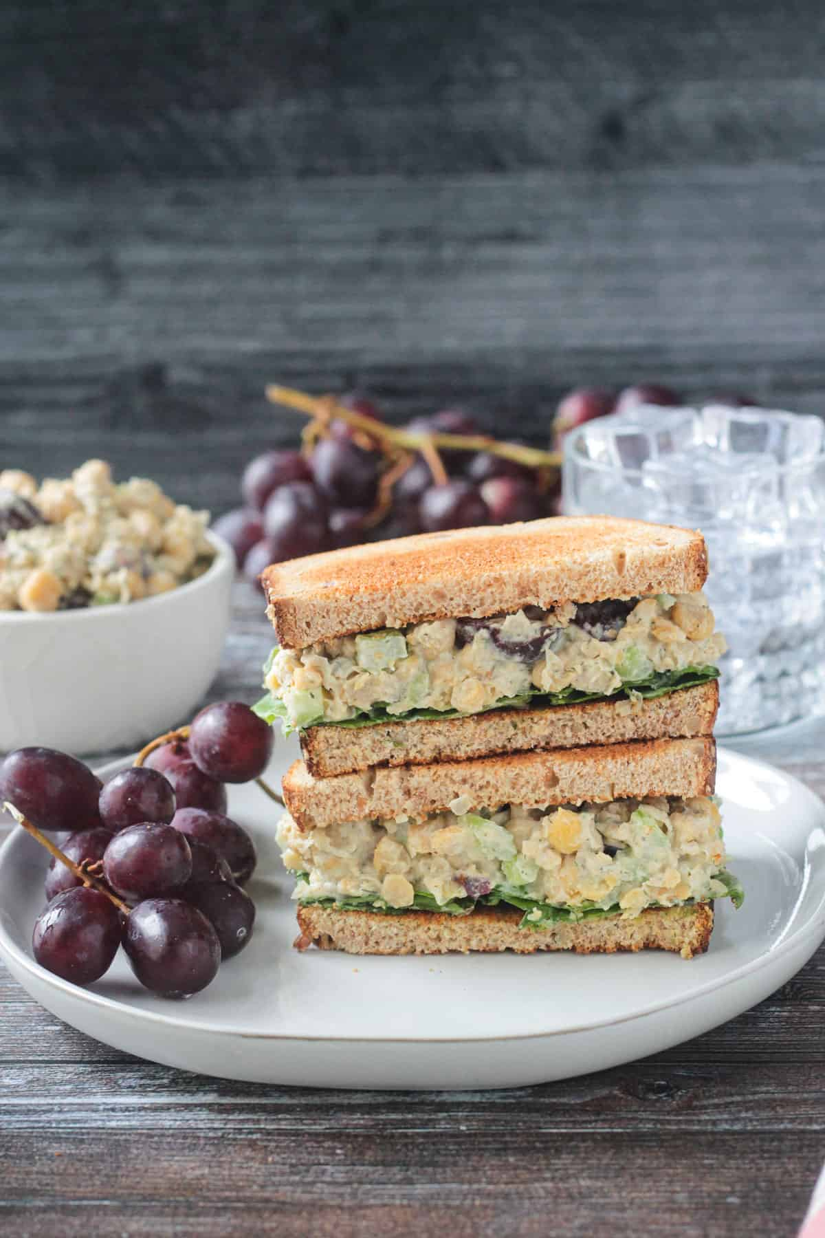 Stacked sandwich halves on a plate with a bunch of red grapes.