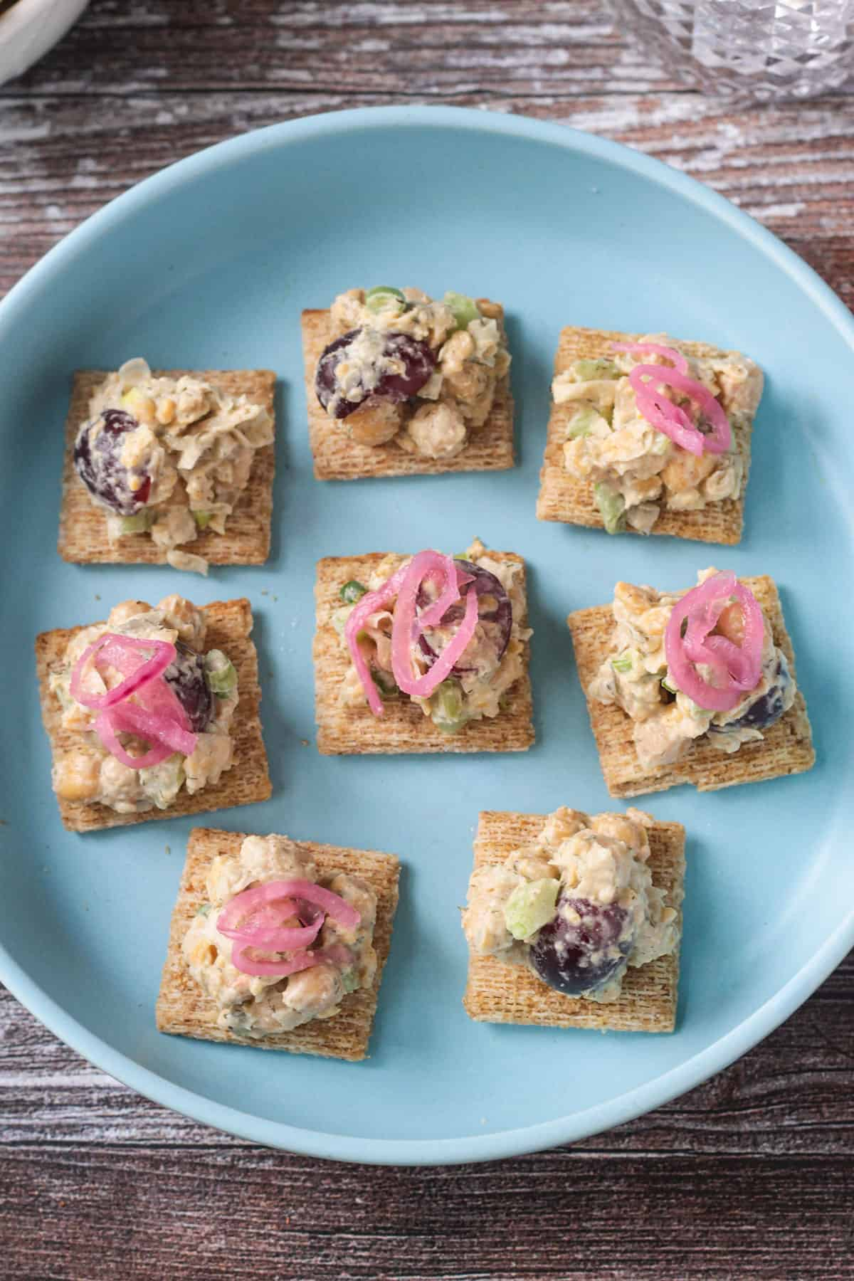 8 wheat crackers topped with chickpea salad and pickled red onions on a blue plate.