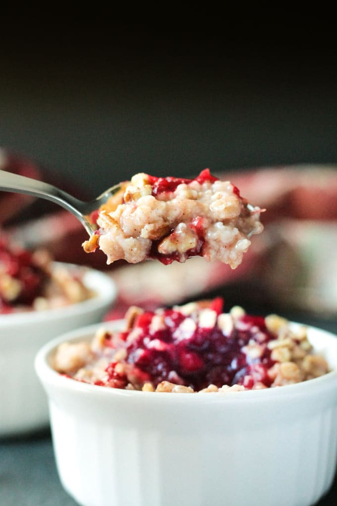 Spoonful of Creamy Cranberry Oatmeal on a spoon over a bowl of more oatmeal.