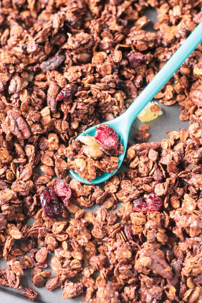 Tray of gingerbread granola with an aqua blue plastic spoon holds a spoonful of granola in the middle of the tray.