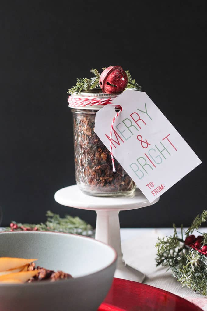 Jar of gingerbread gluten free granola tied with a red/white ribbon and tag that says Merry & Bright. A small red bell and pine needles sit on top of the jar. The jar sits on a small cupcake stand.