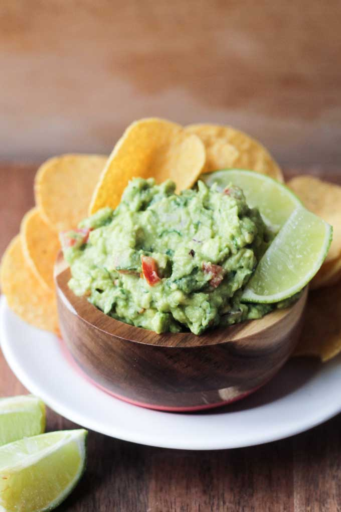 Vegan Guacamole and Chips on a white plate.