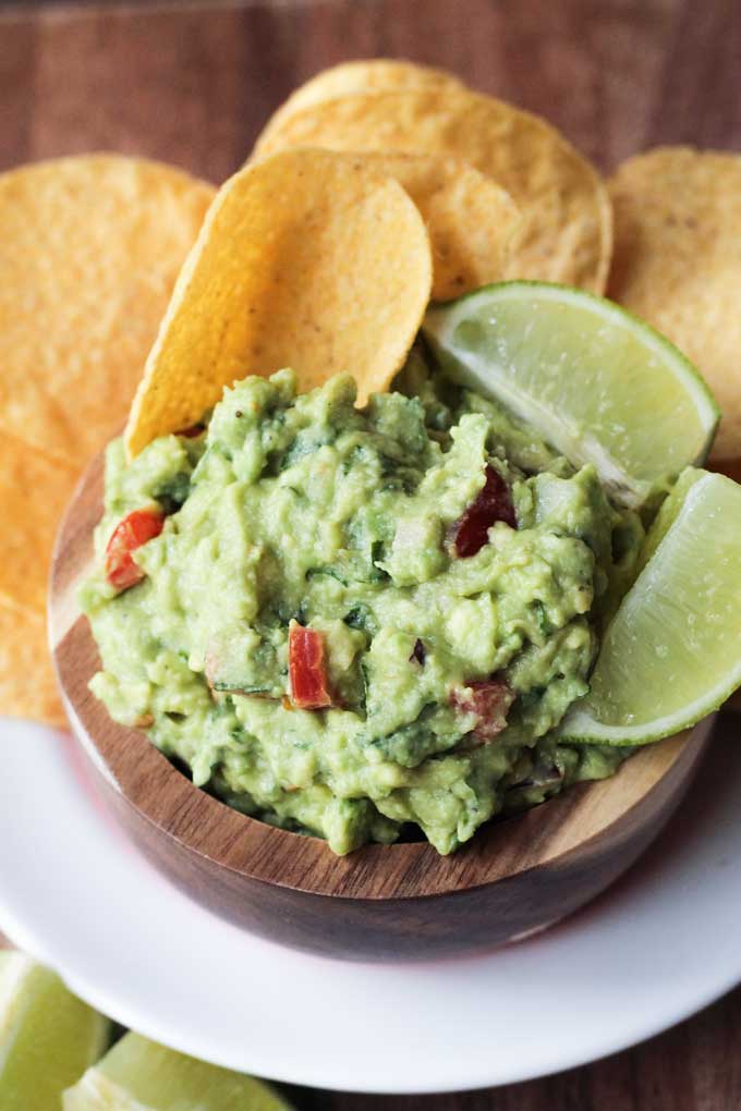 Creamy guacamole in a brown bowl with tortilla chips and lime wedges.