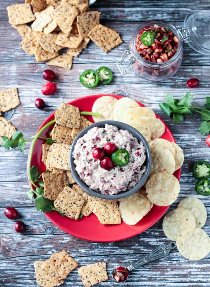 Cranberry Salsa Dip in gray bowl in the middle of a red plate surrounded by tortilla chips and crackers. On the table surrounding the plate are jalapeño slices, cilantro, fresh cranberries, and extra crackers.