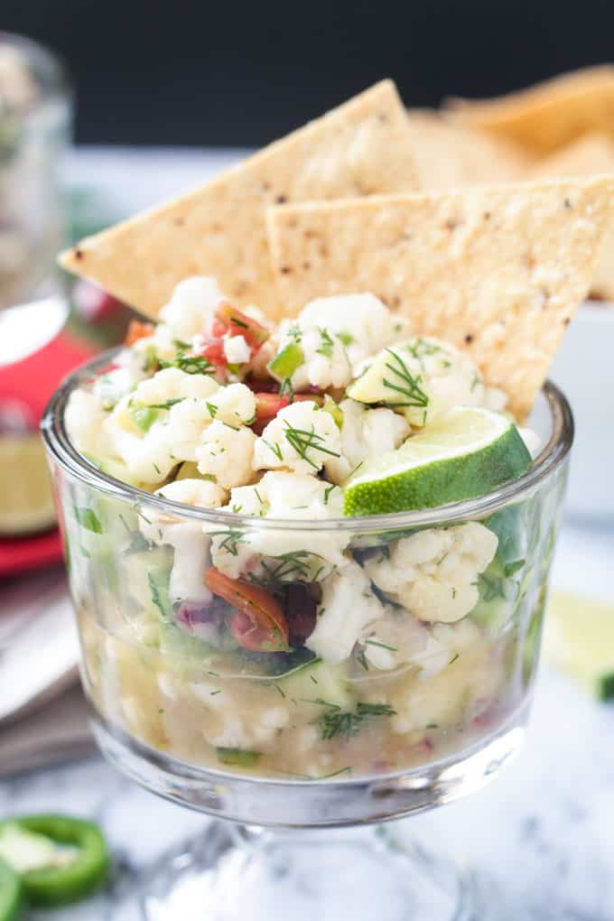 Two tortilla chips stick up from a glass bowl of cauliflower vegan ceviche.