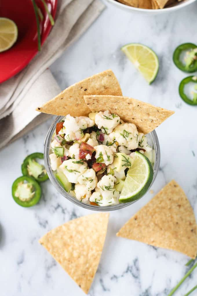Cauliflower vegan ceviche in a bowl on a marble slab surrounded by tortilla chips and jalapeño slices.