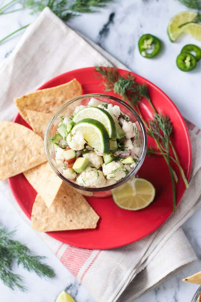 Glass bowl of ceviche, tortilla chips, lime wedge, and fresh dill, all on a red plate.