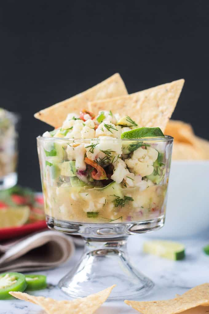Glass bowl of cauliflower ceviche with two tortilla chips sticking out of the top.