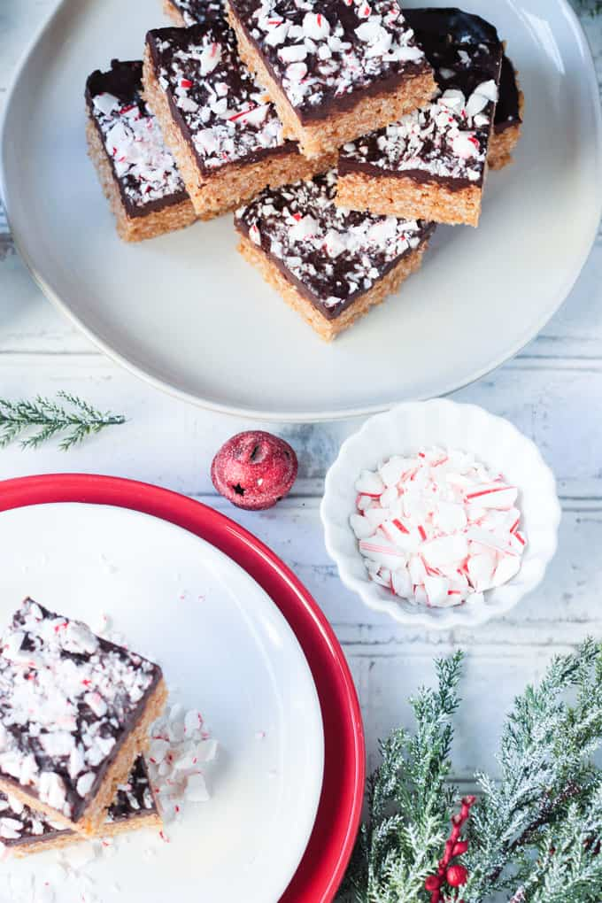 Small bowl of crushed candy canes near a plate of chocolate peppermint rice crispy bars.