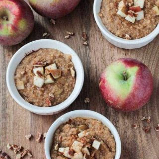 three bowls of oatmeal topped with apples